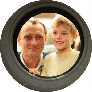 Man and Boy look through the center of a tire