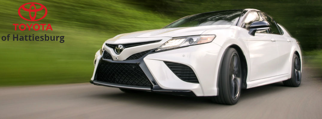 White 2018 Toyota Camry Front Exterior in Motion on Wooded Road