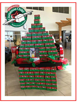 Display of Red and Green Operation Christmas Child Boxes at Toyota of Hattiesburg with Samaritan's Purse Operation Christmas Child Logo