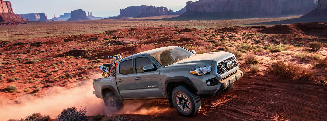 Cement Gray 2018 Toyota Tacoma Climbing Hill in Desert with Dirt Bike in Bed and Rock Formations in Background
