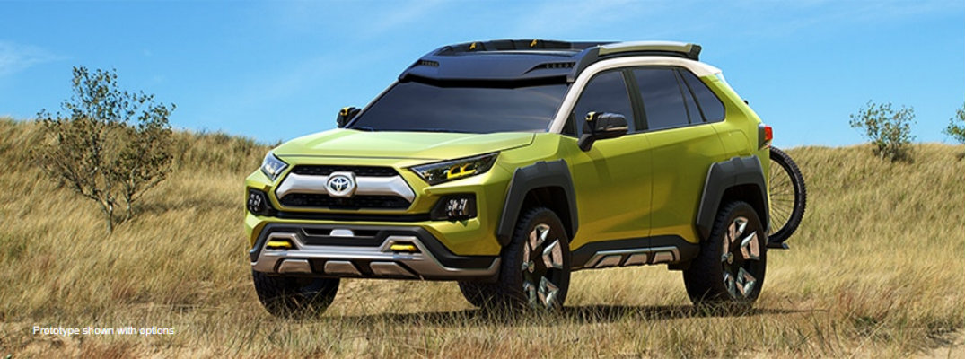 Wide shot of green Toyota FT-AC concept parked in field in daytime