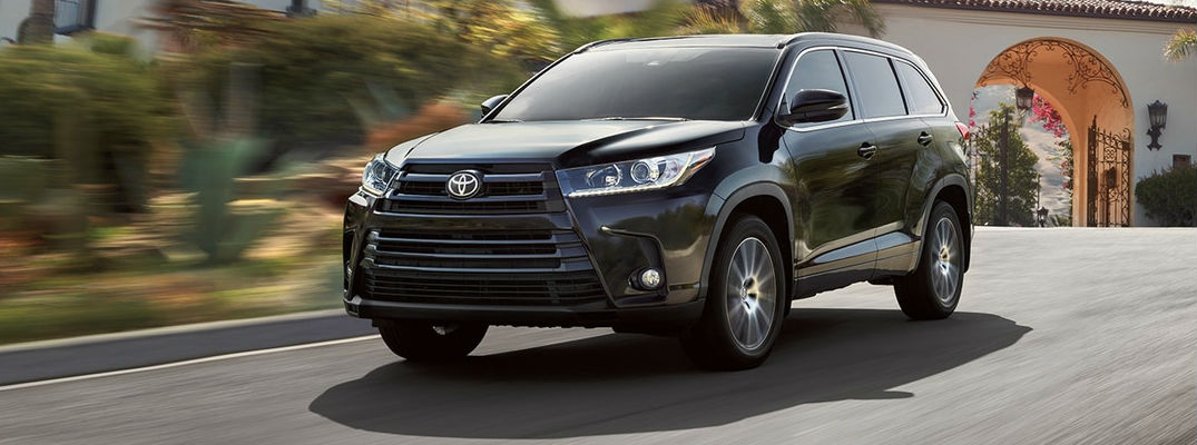 Midnight Black Metallic 2018 Toyota Highlander Driving on City Street