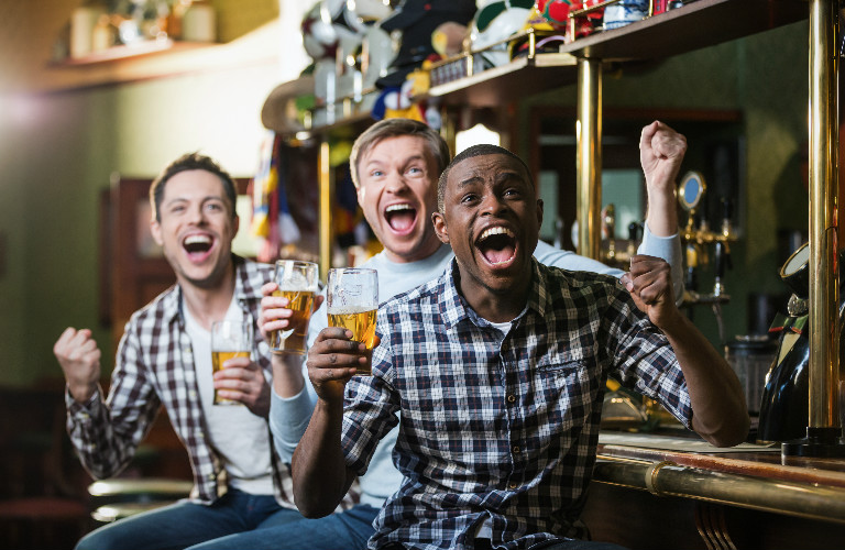 Fans in a Bar Cheering During Football Game