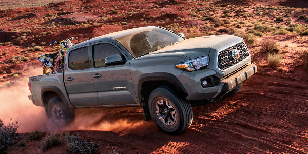 Gray 2018 Toyota Tacoma on Desert Trail with Dirt Bike in Bed