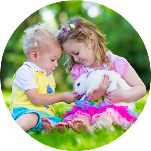 2 Children Sitting on the Grass Holding a White Bunny