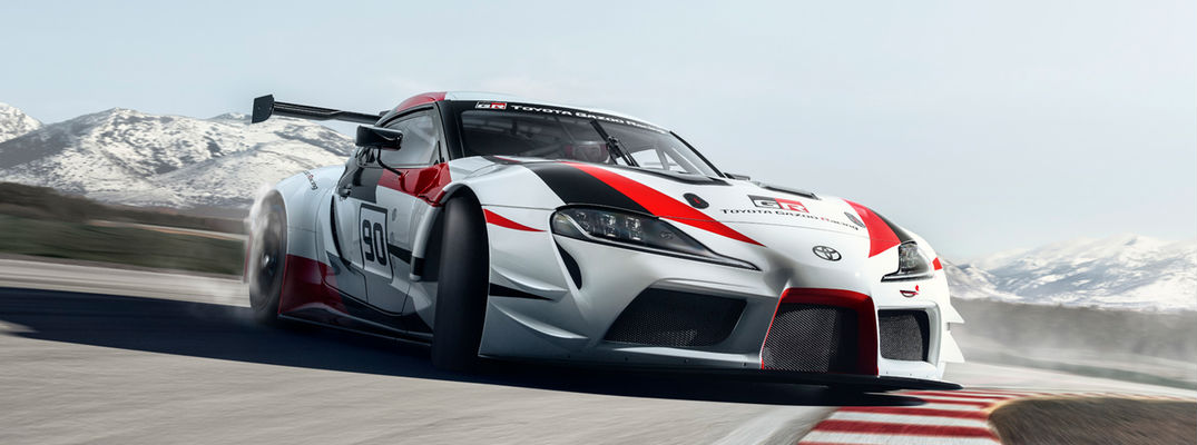 Red, White and Black Toyota GR Supra Concept Front Exterior on Track with Mountains in the Background