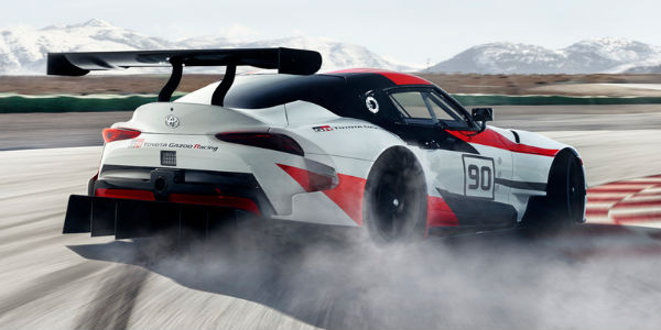 Red, White and Black Toyota GR Supra Concept Rear Exterior on Track with Mountains in Background