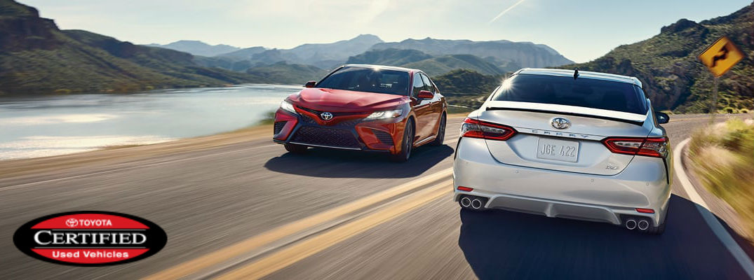 Red and Silver 2018 Toyota Camry Models on Curvy Coast Road with Red and Black Toyota Certified Used Vehicle Badge in Foreground