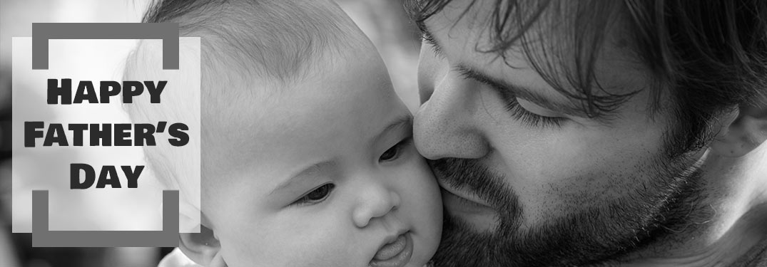 Black and White Image of Dad Holding Child with Black Happy Father's Day Text