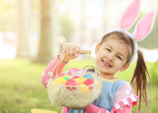 little girl wearing bunny ears holding basket